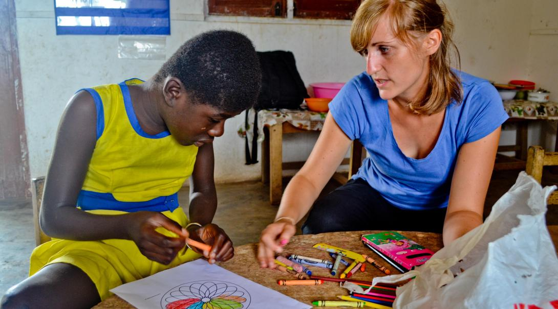 A Projects Abroad volunteer works with a local boy to record and analyze data while doing her speech internship in Ghana.